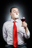 Stop Alcoholism. Man in red tie with plaster on his mouth holding the glass of red wine at black background. Represents outcry alcoholic dependency Stock Images