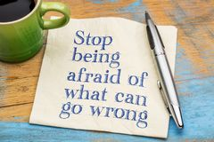 Stop being afraid of what can go wrong. Handwriting on a napkin with a cup of coffee stock photo