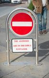 Stop, the Bible holds the answers. Stop sign in red and white with text `the answers are in the bible` in uppercase red letters, part of a street scene stock photography