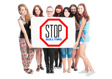 Stop Bullying Concept. Written on cardboard held by a bunch of young girl on white background Stock Photography