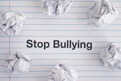 Stop Bullying. Phrase Stop Bullying on notebook sheet with some crumpled paper balls on it. Close up stock photos