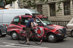 Stop and chat. LONDON, UK - JUNE 11, 2014: A cyclist chats to driver in a line of  stationary taxis during a taxi driver strike Royalty Free Stock Image