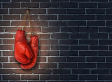 Stop Competing. And putting an end to business competition by hanging up a pair of red boxing gloves on a dark rustic old brick wall as a concept of stopping Royalty Free Stock Photography