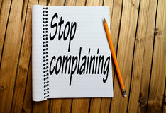 Stop complaining word. On notepad stock photo