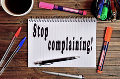 Stop complaining!. Stop complaining written on notebook Royalty Free Stock Photo