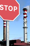 Stop the contamination. Stop traffic sign pointing to a factory casting contaminated gases Royalty Free Stock Photos