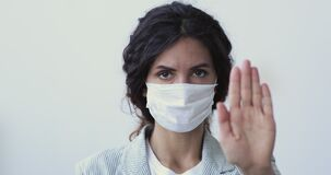 Woman wears medical mask showing stop coronavirus hand gesture