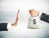 Stop corruption concept. Hand saying no to money bag on abstract background. Stop corruption concept Stock Image