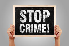 Stop Crime. Blackboard is holden by hands with gray background Stock Photos