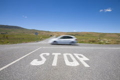 Stop crossroads fast car. Crossroads with stop symbol white painted on asphalt and fast car in rural road next to Madrid Spain Europe Royalty Free Stock Image