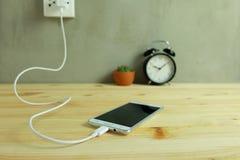 Stop in de lader van het de Adapterkoord van de machtsafzet van mobiele telefoon op houten stock foto