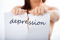 Stop depression. Woman tearing sheet of paper with the word depression Stock Images