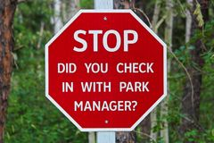 A stop, did you check with the park manager sign.  Royalty Free Stock Photo