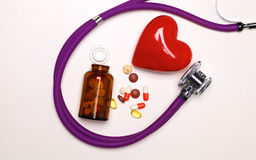 Stop disease. Close up of pills spread over the table with stethoscope and heart lying beside Stock Photos