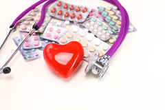 Stop disease. Close up of pills spread over the table with stethoscope and heart lying beside Stock Photography