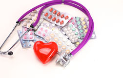 Stop disease. Close up of pills spread over the table with stethoscope and heart lying beside royalty free stock photos