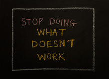STOP DOING WHAT DOES'T WORK, message on black background. Stock Images