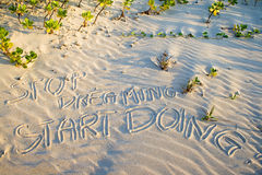Stop dreaming start doing! Creative motivation concept. Stop dreaming start doing! Creative motivation concept written in the sand at the beach Stock Photography