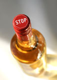 Stop drinking. Full spirits bottle with stop sign on top stock image