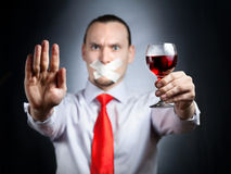 Stop drinking alcohol. Businessman with plaster on his mouth in red tie holding the glass of red wine and gesturing stop sign by his palm at black background Stock Photography