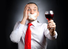 Stop drinking alcohol. Despair Businessman with plaster on his mouth in red tie holding the glass of red wine and at black background. Represents outcry Royalty Free Stock Photo