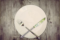Stop eat concept. Wooden table with empty plate and crossed silver cutlery symbolizing to refuse food Stock Images