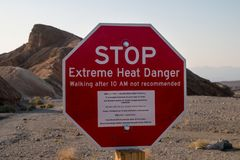 Stop! Extreme heat danger landmark red sign in the hot ridges of Zabriskie Point, Death Valley National Park, California, USA royalty free stock images