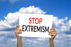 STOP EXTREMISM card in hand against blue sky with clouds. Royalty Free Stock Images