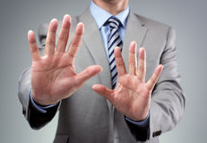 Stop. Or fear gesture from businessman in suit holding hands up stock image