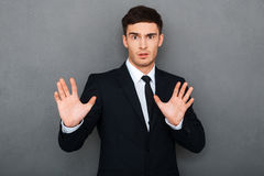 Stop it!. Frustrated young man in formalwear keeping arms raised and expressing negativity while standing against grey background Royalty Free Stock Image