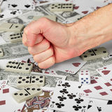 Stop gambling!. The hand clenched in a fist against the background of cards and money Stock Photos