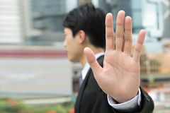Stop gesture. Side view of Asian businessman standing in the city stock photo
