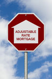 Stop getting a adjustable rate mortgages Road Sign. Red and White Stop Sign with words adjustable rate mortgage with home symbol with sky background Stock Images