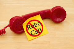 Stop getting a call from a Robocall. Retro red phone handset with a yellow sticky note and text Robocall with not icon Stock Image