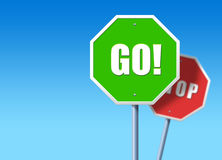 Stop, Go. Green traffic sign saying GO, in front of regular red STOP sign Royalty Free Stock Image