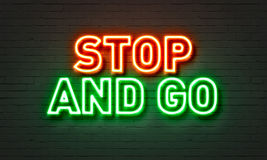 Stop and go neon sign on brick wall background. Royalty Free Stock Photos