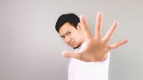 Stop hand sign. An asian man with white t-shirt and grey background royalty free stock images