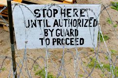 Stop here - military board in barbed wire Stock Image
