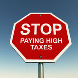 Stop high taxes. Stop paying high taxes on a red stop signboard, concept of investment and tax saving schemes Stock Image