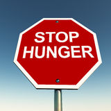 Stop hunger. Stop signboard with stop hunger text against a blue sky, helping and caring for the poor and hungry concept Stock Photo