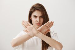 Stop, I hate such attitude. Portrait of angry displeased attractive european girl showing stop, no or dislike gesture stock images