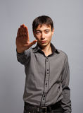 Stop this immediately. Young man in steel-blue shirt standing on grey background with stopping gesture Royalty Free Stock Images