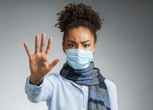 Stop the infection! Healthy woman showing gesture `stop`. Photo of african american woman wears protective mask against infectious diseases and flu on gray stock photo