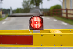 Stop light on barrier. A red light on a yellow barrier, stopping traffic on a countryside road Stock Photo