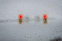 Stop Light Rain Drops. Stop light behind a rain covered car window Stock Photo