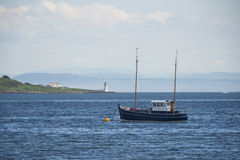 Stop at the lighthouse. Sailing-ship stop at the lighthouse stock photography