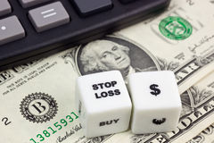 Stop loss US dollar. US currency with calculator and dice showing STOP LOSS Royalty Free Stock Image