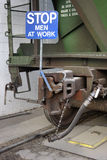 Stop men at work sign on railroad car. Stop men at work sign on a hopper railroad car downloading grain at elevator siding track Stock Photo