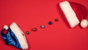 Stop motion animation of New Years balls and Santa Claus hat. Flat lay of Christmas balls and red and blue hat.