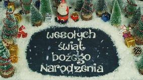 Stop motion animation of Wesołych świąt Bożego Narodzenia Polish, in English Merry Christmas. Stop motion gift box Santa Claus decoration on snow for Royalty Free Stock Images